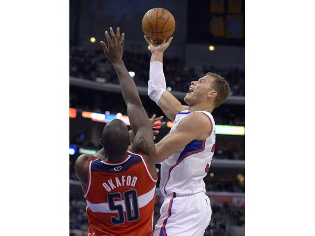 Los Angeles Clippers forward Blake Griffin, right, puts up a shot against Washington Wizards center Emeka Okafor during the first half on Saturday in Los Angeles.