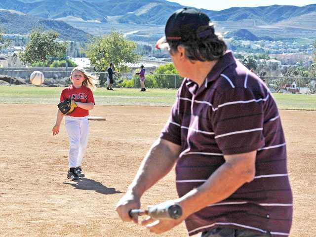 Campbell Heger, 7, pitches to her grandfather Ken Heger as they enjoy a game a baseball at Canyon Country Park on Monday. Signal photo by Jonathan Pobre