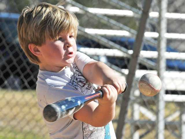 Kyle Heger, 5, eyes the ball as he enjoys spring-like weather with a game of baseball with his sister, father and grandfather at Canyon Country Park on Monday. Signal photo by Jonathan Pobre