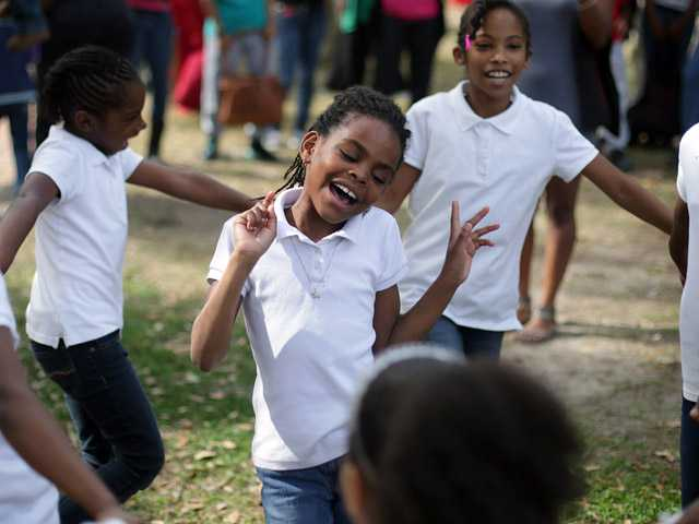 "Kalylah Carter, 8, sings Beyonce's ""Love on Top"" as other G.E.M.S. with God's Servant Ministries dance in a circle during Martin Luther King, Jr. Day celebrations at McKenzie Park on Monday in Panama City, Fla."