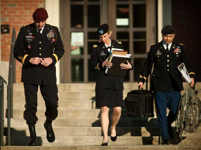 Army Brig. Gen. Jeffrey A. Sinclair, left, leaves a Fort Bragg, N.C. courthouse with his defense team.