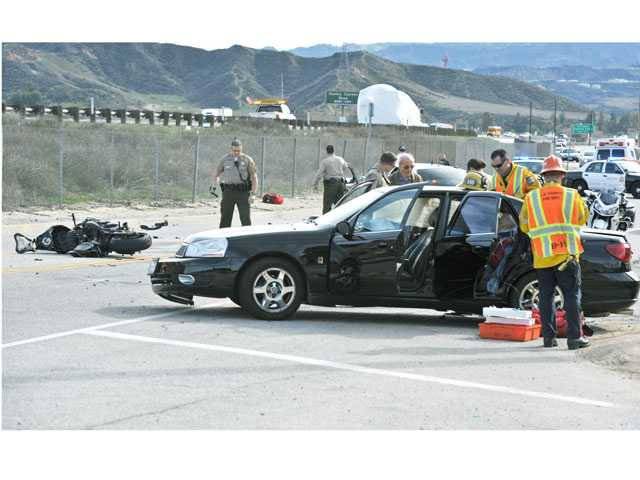 California Highway Patrol officers, sheriff's deputies and firefighters work the scene of a three-car crash on The Old Road near Wedgewood Court in Castaic on Tuesday. Signal photo by Jonathan Pobre