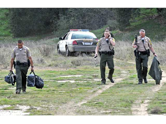 Sheriff's deputies pull gear from a patrol vehicle involved in a crash with two other vehicles on The Old Road near Wedgewood Court in Castaic on Tuesday. Signal photo by Jonathan Pobre