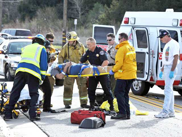 First responders lift an injured motorist to a waiting ambulance at the scene of a three-car crash in Castaic on Tuesday. Signal photo by Jonathan Pobre