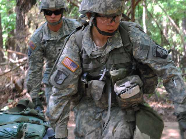 Capt. Sara Rodriguez, 26, of the 101st Airborne Division, carries a litter of sandbags during the Expert Field Medical Badge training at Fort Campbell, Ky.