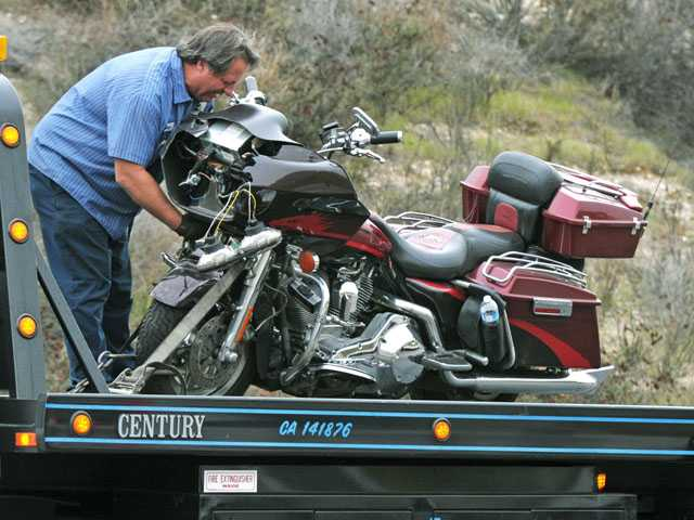 A tow truck driver secures to his truck a motorcycle that was involved in a collision Wednesday on Golden Valley Road near Robert C. Lee Parkway. Signal photo by Jonathan Pobre