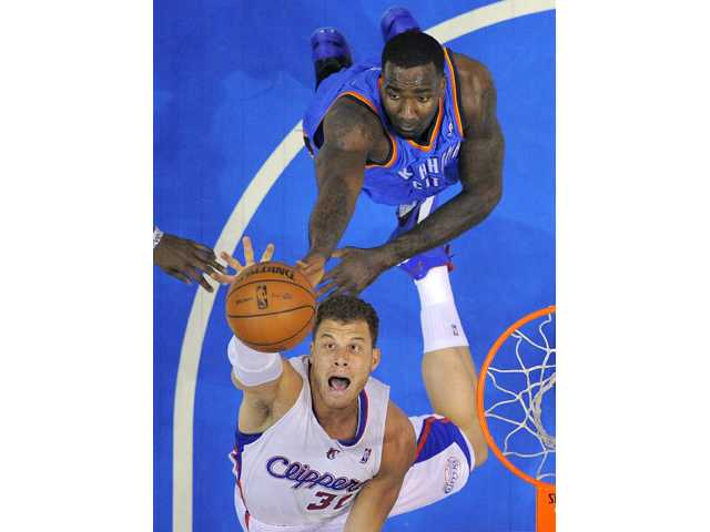 Los Angeles Clippers forward Blake Griffin, below, goes after a rebound along with Oklahoma City Thunder center Kendrick Perkins on Tuesday on in Los Angeles.