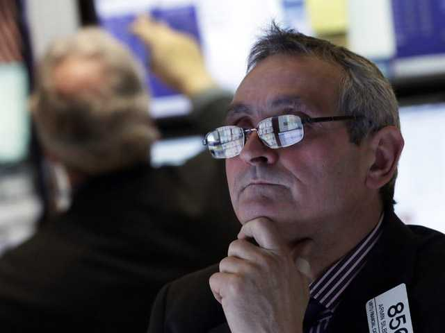 The screens of specialist Armin Silbersmith are reflected in his glasses as he works at his post on the floor of the New York Stock Exchange.