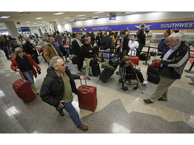 Stranded passengers wait in line at the Southwest ticket counter at the Salt Lake City Airport Thursday.