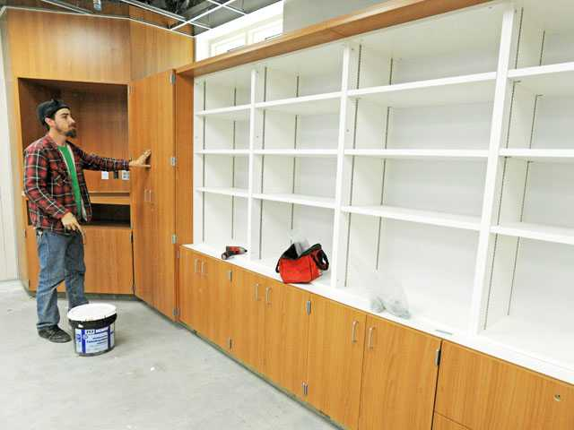 Donald Potter with Pieri Woodworks installs a cabinet in a classroom in the new two-story classroom building under construction at Emblem Elementary School in Saugus on Tuesday