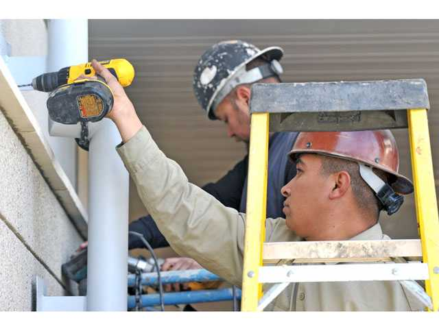 Francisco Guerrero, front, and Carlos Ferreira install piping along the exterior of the new classroom building under construction at Emblem Elementary School in Saugus on Tuesday