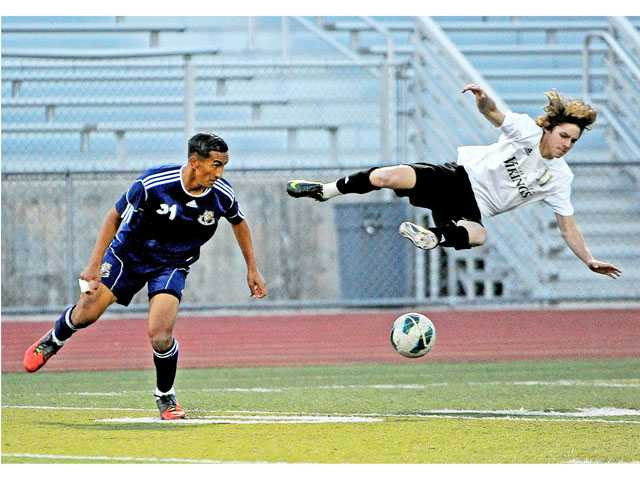 Valencia's Ian Canevari gets upended by West Ranch's Jake Martinez in the first half of the their game on Tuesday at Valencia High. Valencia won the game 1-0.