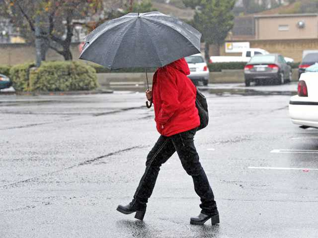 A woman walks across a rain-slicked parking lot outside the 99 Cents Only store on Lyons Avenue in Newhall on Thursday morning. Signal photo by Jonathan Pobre