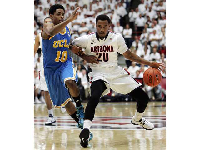 Arizona's Jordin Mayes (20) drives against UCLA's Larry Drew II during the first half of an NCAA college basketball game.