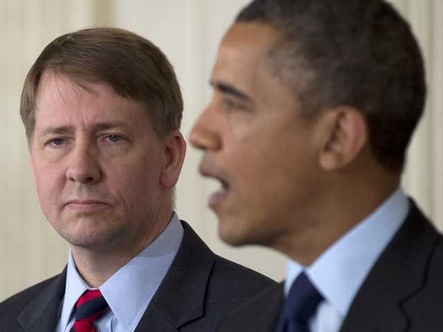 Richard Cordray stands left as President Barack Obama announces in the State Dining Room of the White House in Washington.