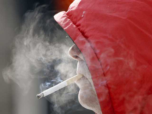 A man smokes in Omaha, Neb. Annual health care costs are roughly $96 billion for smokers and $147 billion for the obese, the government says.