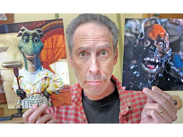 "Trautman with photos of two of his characters — the character of ""Fran"" from the 1990s TV show ""Dinosaurs"", left, and ""Tarman"" from the horror feature film ""Return of the Living Dead."" Trautman will sign autographs next weekend in Atlanta for ""Tarman"" fans."
