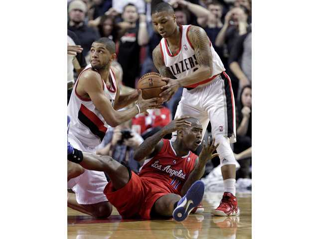 Los Angeles Clippers guard Jamal Crawford, on floor, reacts to a jump ball call as the Portland Trail Blazers' Damian Lillard, right, and Nicolas Batum hold the ball in Portland, Ore., on Saturday.