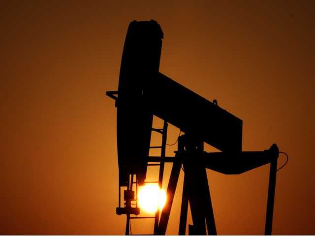 An oil pump works at sunset in the desert oil fields of Sakhir, Bahrain, on Tuesday. (AP)
