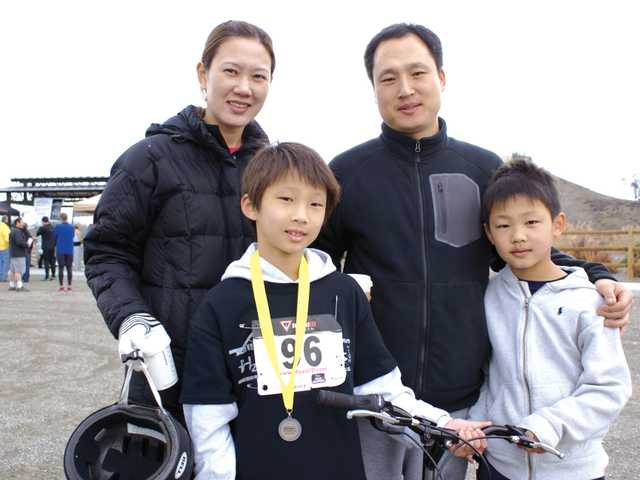 Duathlon competitor No. 96 Brent Lee, 9, is joined at the finish line Sunday morning by his parents, Alex and Monica Lee, and his younger brother Michael. (Jim Holt/The Signal)