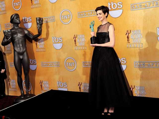"Actress Anne Hathaway poses backstage with the award for best female actor in a supporting role for ""Les Miserables"" at the 19th Annual Screen Actors Guild Awards."