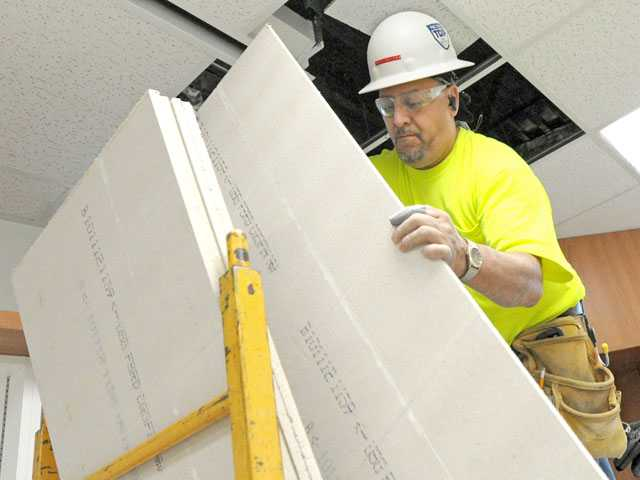 Pete Santos with Advanced Interiors installs acoustical ceiling panels in the new classroom building under construction at Emblem Elementary School in Saugus on Jan. 22.