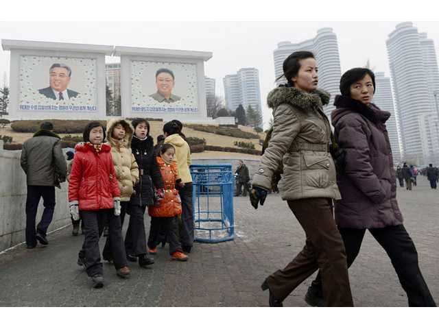 People walk near giant portraits of late North Korean leaders, Kim Il Sung, left, and his son Kim Jong Il, in Pyongyang, North Korea.
