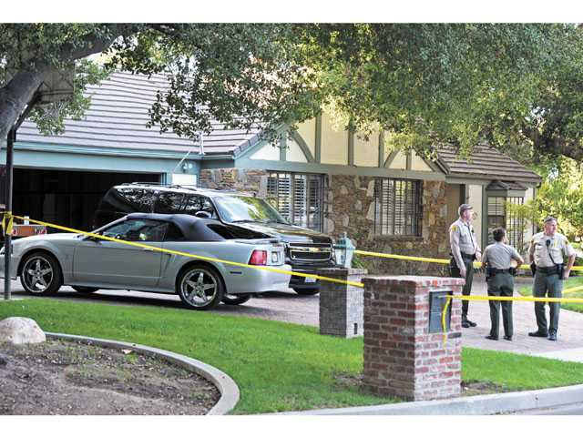 Sheriff's deputies work a scene where a man and a woman were found dead at a home at Heritage Lane and Maple Street in Newhall, Monday, Oct. 15, 2012.