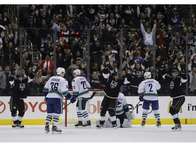 Members of the Los Angeles Kings celebrate defenseman Slava Voynov's game-tying goal against the Vancouver Canucks on Monday in Los Angeles.