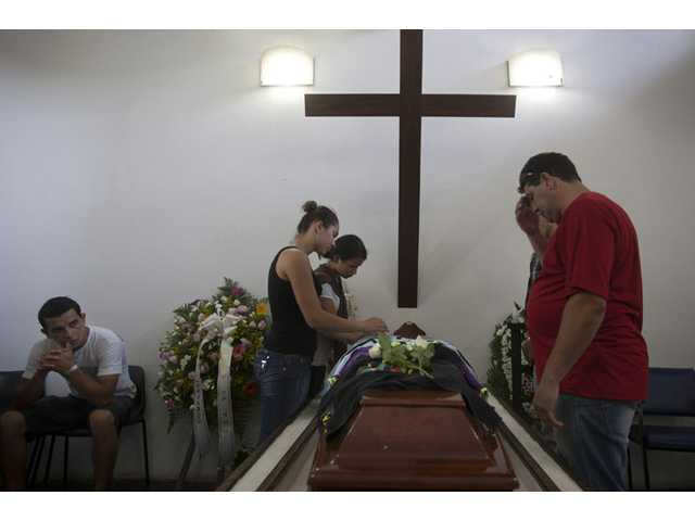 People attend the funeral of Gustavo Goncalves, the most recent victim of the Kiss nightclub fatal fire.