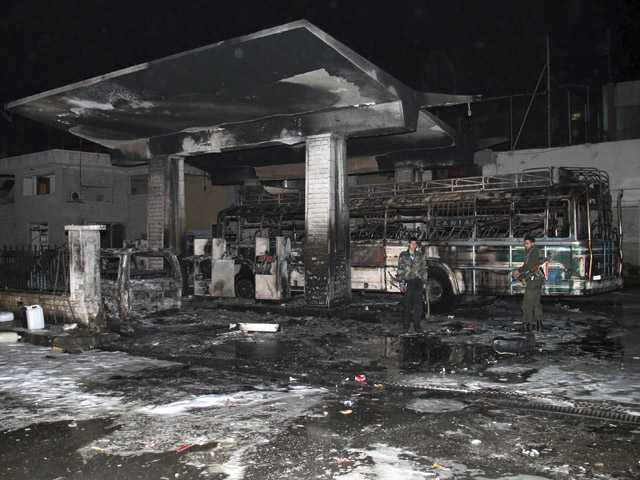 In this Jan. 3 photo, Syrian security officers check a gas station that was attacked by a car bomb, killing several people.