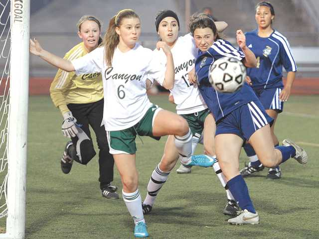 Canyon's Hanna Halstead (6) and West Ranch's Ashley Goodin (11) meet at the goal at Canyon on Tuesday.