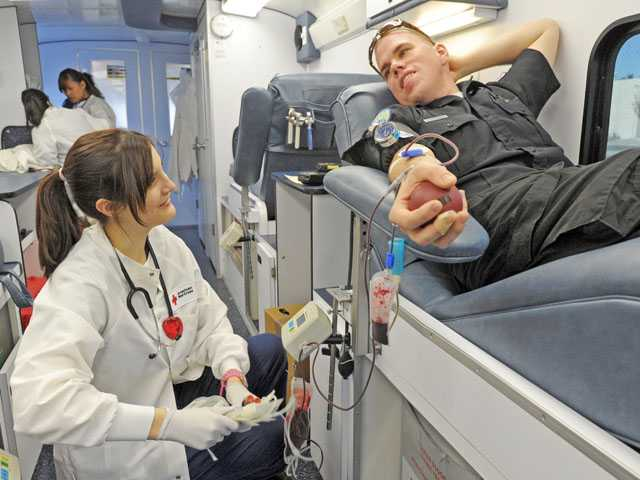 "Blood collection tech Nicole Pena, left, chats with EMT Joshua Pierce as he donates blood Wednesday during the ""Battle of the Badges"" blood drive. Signal photo by Jonathan Pobre"