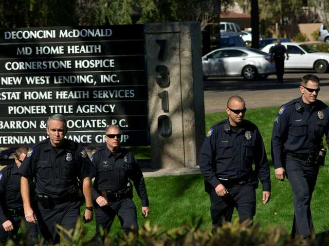 Police officers leave an office building after a shooting at the building in Phoenix on Wednesday. A gunman opened fire at the Phoenix office building, wounding three people.