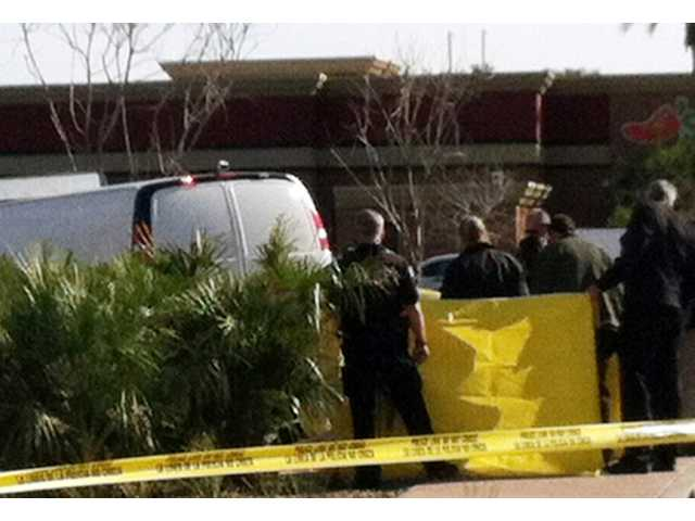 Arizona officials check a body found in bushes by a landscaper in the Phoenix suburb of Mesa, Arizona.