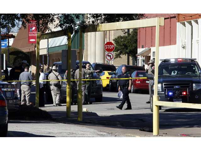Law enforcement officers investigate the scene of a shooting in downtown Kaufman, Texas on Thursday.