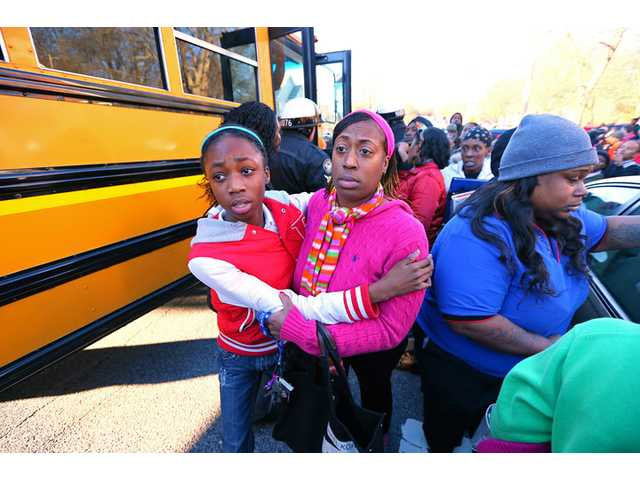 Mother and daughter embrace as Tiffany Myricle, 37, leads her daughter Xavia Denise Myricle away from her school bus.
