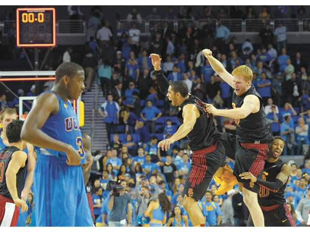 USC players celebrate as UCLA's Jordan Adams, left, looks on Wednesday in Los Angeles. USC won 75-71.