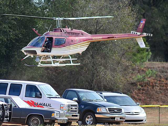 The Dale County Sheriffs Department helicopter lands at the scene of an ongoing hostage crisis in Midland City, Ala.