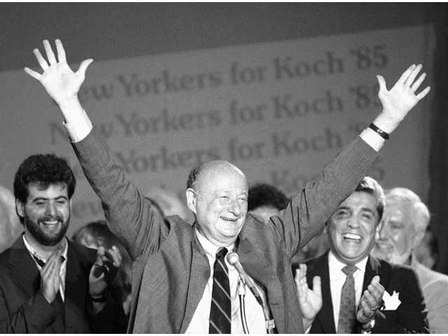 In this Sept. 11, 1985 file photo, New York Mayor Ed Koch raises his arms in victory.