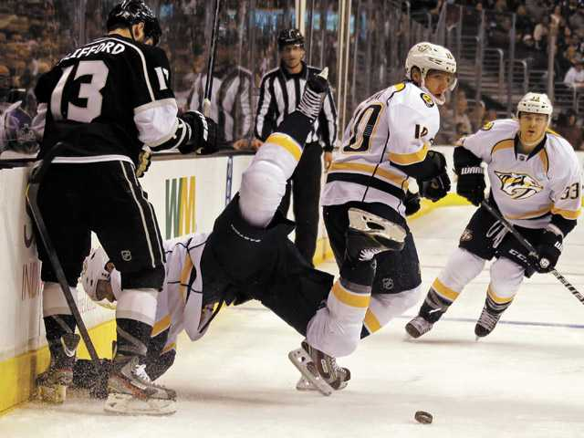 Nashville Predators defenseman Kevin Klein (8) goes flying while left winger Martin Erat (10) and center Colin Wilson (33) chase the puck as Los Angeles Kings left winger Kyle Clifford watches in Los Angeles on Thursday.