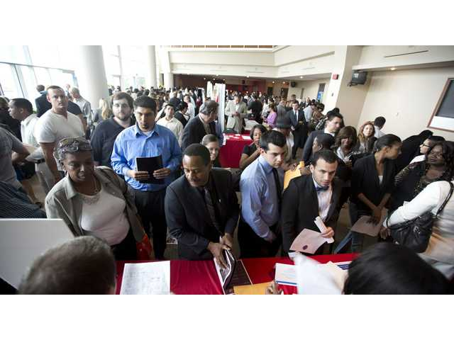 Job seekers fill a room at the job fair in Sunrise, Fla.