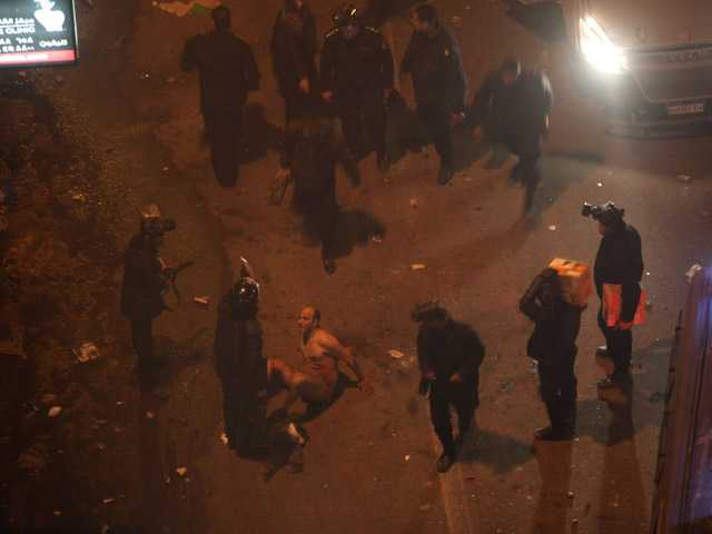 Egyptian riot police beat a man, after stripping him during clashes next to the presidential palace, Friday.