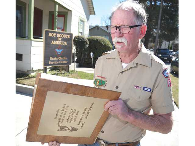 Dave McEachern stands in front of the Boy Scouts of America Service Center in Newhall as he holds his son James' Eagle Scout honor book and discusses the Boy Scouts of America's policy on allowing gays in the organization. (Dan Watson/The Signal)