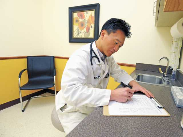 Dr. Steve Yi looks over a chart in an exam room at Valencia Medical Care. (Jonathan Pobre/The Signal)
