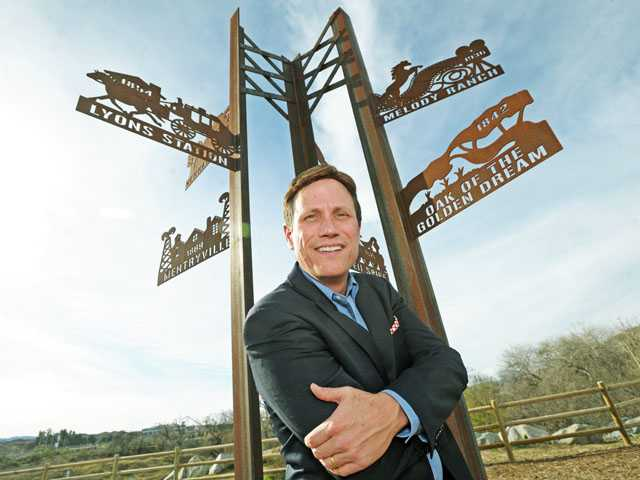 """Dow, with the """"Crossroads"""" art piece, by Dianne Foderano and Idelle Okman Tyzbir, at the Iron Horse Trailhead in Valencia. Dow was appointed to the Arts Commission by Mayor Bob Kellar in 2009. He is one of the five founding members of the commission. (Jonathan Pobre/The Signal)"""