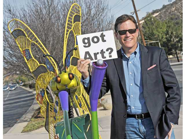 "John Dow, chairman of the Santa Clarita Arts Commission, with the ""Western Tiger Swallowtail"" sculpture, by LT Mustardseed, along Bouquet Canyon Road near Central Park in Saugus. (Jonathan Pobre/The Signal)"
