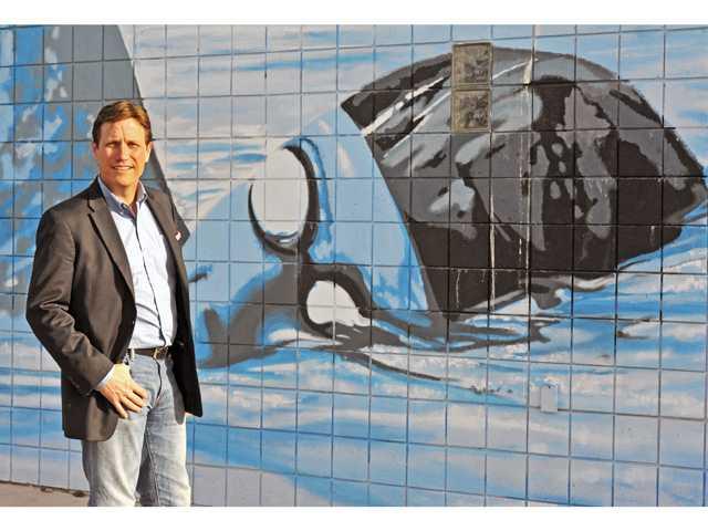 "Dow with ""The Final Lap,"" by artist Bob Hernandez, at the Santa Clarita Aquatic Center. (Jonathan Pobre/The Signal)"