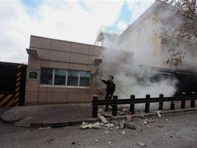 An embassy security guard asks for help at the US embassy just minutes after a suicide bomber has detonated an explosive device at the entrance of the U.S. Embassy in the Turkish capital, Ankara, Turkey, Friday, Feb. 1, 2013, At least two people are dead, officials said.