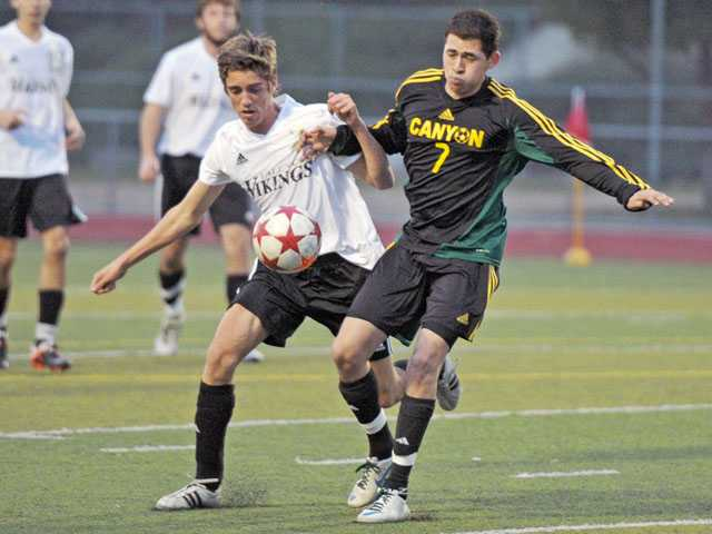 Valencia's Colton Morgan, left, and Canyon's Bonifacio Rojas vie for possession on Friday at Valencia High. The Vikings stayed one point back of first with a 4-0 win.